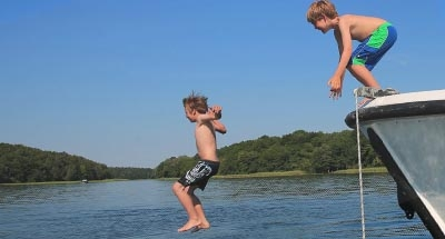 Children jumping off front of boat